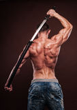 Man with sword. Shirtless young man posing with katana sword Royalty Free Stock Images