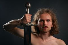 Man with sword. On grey Royalty Free Stock Photo