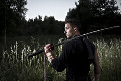 Man with sword. Attractive man with sword during sunset on the field Stock Photography