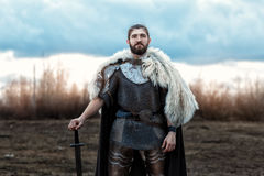 Man with a sword defenseman. Formidable man warrior in armor and sword standing in a field and protects Stock Image