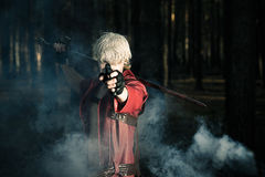 Man with a sword and a gun in the hands. Of a smoky the forest Royalty Free Stock Photo