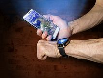 Athlete syncs your smartphone and smart watch on on your hand stock photo