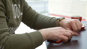 Man synchronizing smartwatch with smartphone in cafe stock footage