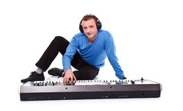 Man with synthesizer. Young man posing with synthesizer and headset over white background royalty free stock photo