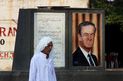 Man in Syria. A man in Bosra, Syria, passing by a picture of Hafez al-Assad, the former president stock photos