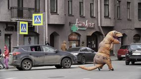 Man in t rex costume running at city street crosswalk. With lots of parked cars. Sunny day. Slow motion stock video