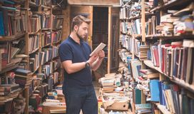 Man in a T-shirt and a beard stands in an old public library with a book in his hands. A student is looking for books in an old library. Self-education stock photos