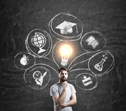 Man in T-shirt and blackboard with education sketches. Portrait of man in T-shirt standing near blackboard with glowing light bulb above his head and education Royalty Free Stock Photos