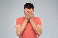 Man in t-shirt covering his face with hands. People, crisis, emotions and stress concept - man in t-shirt covering his face with hands over gray background Stock Images