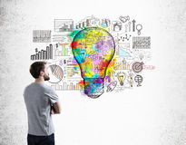 Man in T-shirt and light bulb. Side view of man in T-shirt examining startup sketch on concrete wall with colorful light bulb icon in center. Concept of small Stock Photography