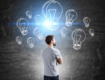 Man in T-shirt and light bulbs Royalty Free Stock Photo