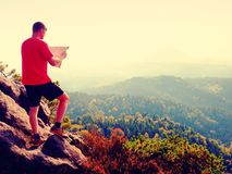 Man in t-shirt and pants on mountain top watching into opened landscape and check the map. Rainforest valley Royalty Free Stock Images