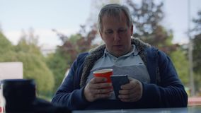 Man in t-shirt with paper cup of coffee surches internet in his smartphone stock footage