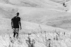 Man in T Shirt and Shorts Standing on Grass Field Grayscale Photography Stock Images