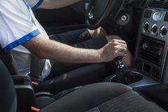Man in the T-shirt sits behind the wheel of a passenger car and holds a hand on the gear lever. The man in the T-shirt sits behind the wheel of a passenger car stock photo