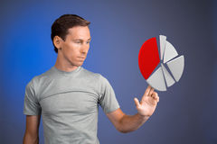 Man in t-shirt working with pie chart on blue background. Stock Images