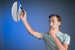 Man in t-shirt working with pie chart on blue background. Young man in t-shirt working with pie chart on blue background. Concept on the topic of statistics or Royalty Free Stock Photos