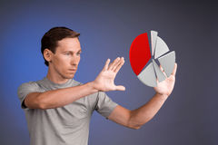 Man in t-shirt working with pie chart on blue background. Young man in t-shirt working with pie chart on blue background. Concept on the topic of statistics or Royalty Free Stock Image