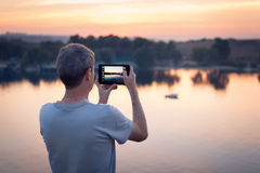 Man with tab makes photo of the sunset Stock Images