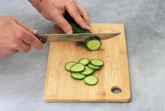 Man at the table cuts a cucumber on a cutting board royalty free stock photos