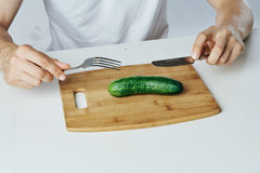 Man at the table eating a cucumber on a cutting board, vegetables, diet, vegetarian royalty free stock photography