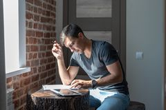 The man at the table in front of the window uses a tablet, work at home, freelance, business plan, bill payment, startup. Man at table in front of window, uses stock photo