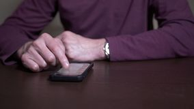 Man at Table Scrolls Through Social Media Feeds on His Mobile Phone. 8484 A slow dolly shot of an unidentifiable man sitting at a table scrolls through various stock footage