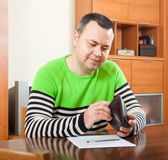 Man at  table with  wallet Stock Photography