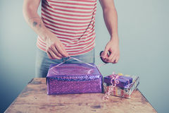 Man at table wrapping presents Stock Images