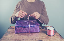 Man at table wrapping presents Stock Photography