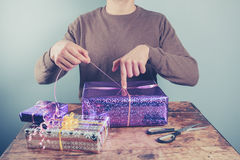Man at table wrapping presents Royalty Free Stock Photography