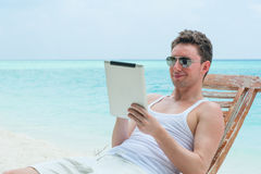Man with tablet on beach, sea view Royalty Free Stock Photo