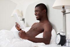 Man tablet bedroom Stock Photo