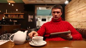 Man with tablet computer drinking tea in cafe stock video
