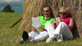 Man with tablet computer and woman with smartphone sits near a haystack stock video footage