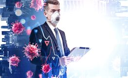 Man with tablet and coronavirus. Young businessman in mask with tablet standing in blurry office with double exposure of coronavirus and falling graphs. Toned