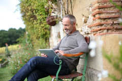 Man with tablet enjoying country house Stock Photo