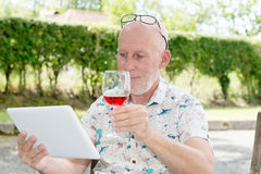 Man with  tablet and glass of red wine in  garden Stock Photography