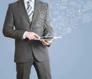 Man with tablet in hands and business sketches Royalty Free Stock Photo
