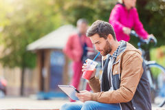 Man with tablet. Handsome young man with tablet outside in the town Stock Photography