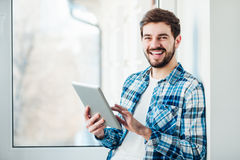 Man with a tablet in his hands. Happy young man smiling into the camera with a tablet in his hands Royalty Free Stock Image