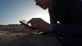 Man tablet. man holding a tablet, on the web page Internet flips through the silhouette of sunset Stock Photos