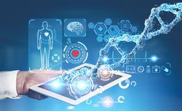 Man with tablet, medical HUD, DNA blue. Man s hand with a digital tablet near a medical HUD and DNA against a blurred blue background. Toned image double royalty free stock photos