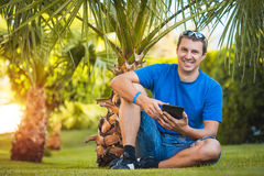 Man with tablet in the palm garden Royalty Free Stock Images