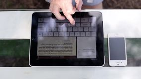 Man With tablet In The Park. Man working with the tablet in a cafe near the park stock video footage
