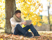 Man with tablet pc in autumn park Royalty Free Stock Photography