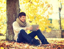 Man with tablet pc in autumn park Royalty Free Stock Photo