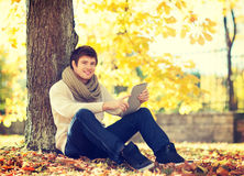 Man with tablet pc in autumn park Stock Photos
