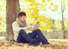Man with tablet pc in autumn park Stock Photography