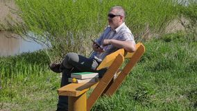Man with tablet PC and books on bench near river stock video